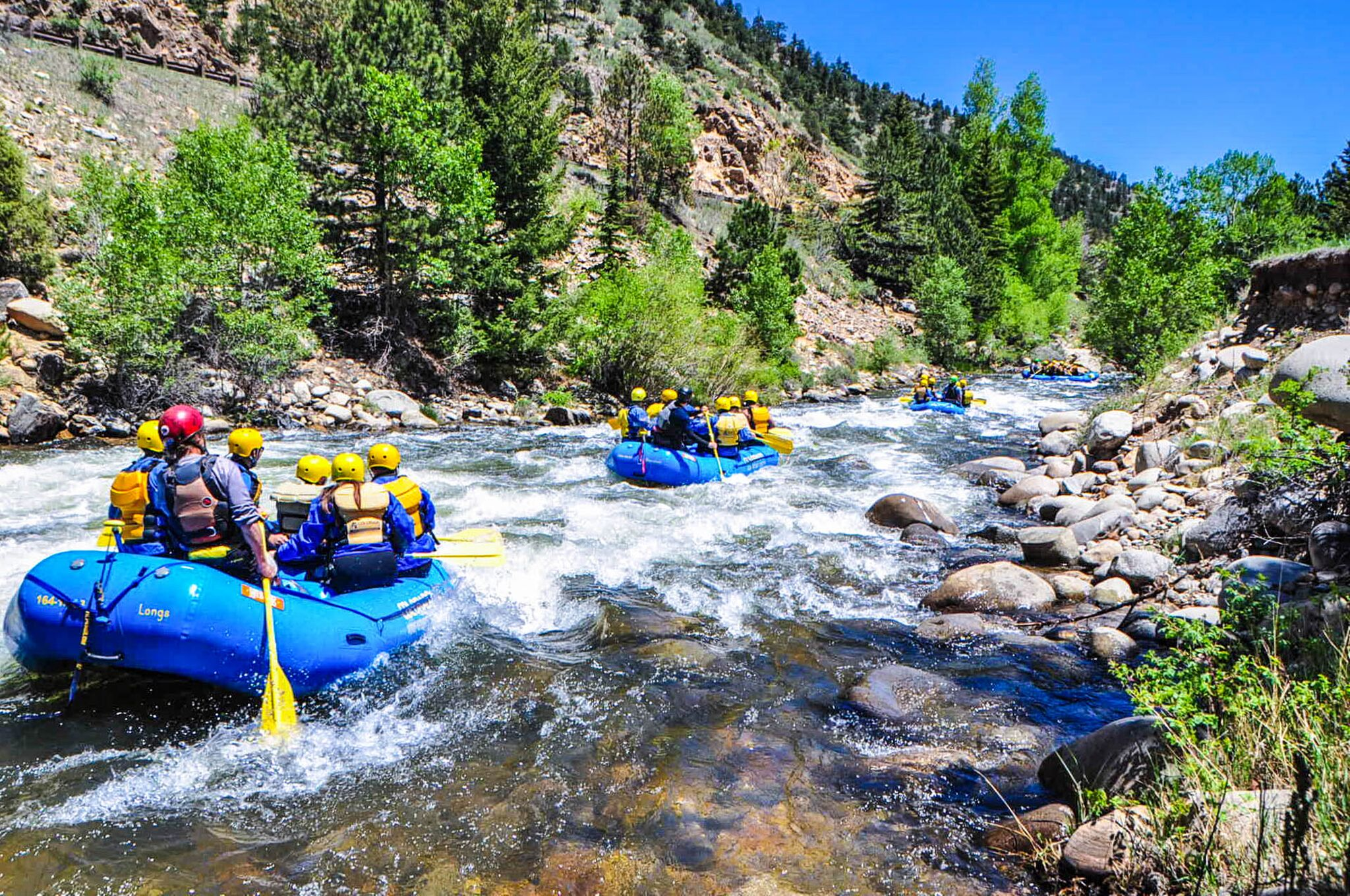 two groups of people rafting down river
